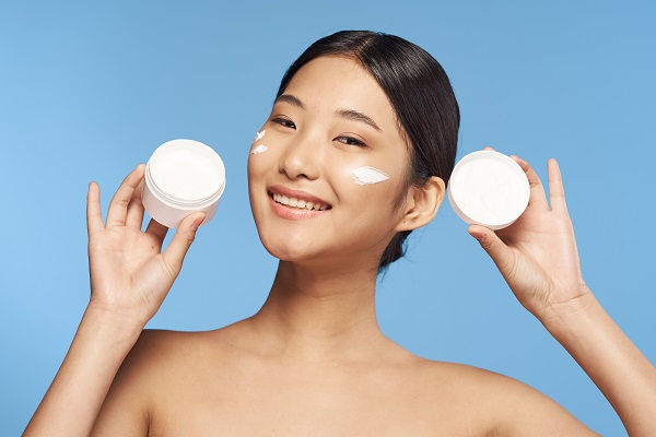 Woman holding moisturizer with cream on her face